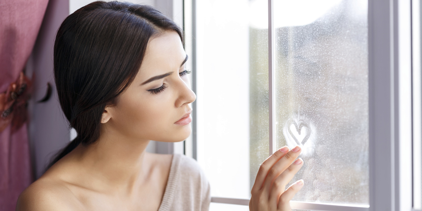 beautiful-lady-drawing-heart-at-window