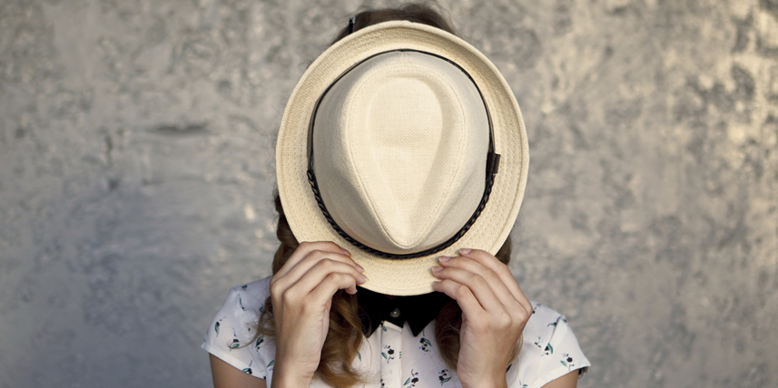 woman-hiding-behind-a-hat